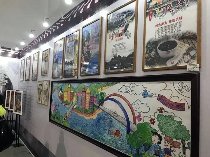 """""""中小学生宝石手工平面粘贴画作品和中学生书画作品展示区""""的梧州市第八中学艺术展示区内,市民群众除了可欣赏到八中学生的艺术作品外,还可以现场体验书法、板画、陶土等制作."""