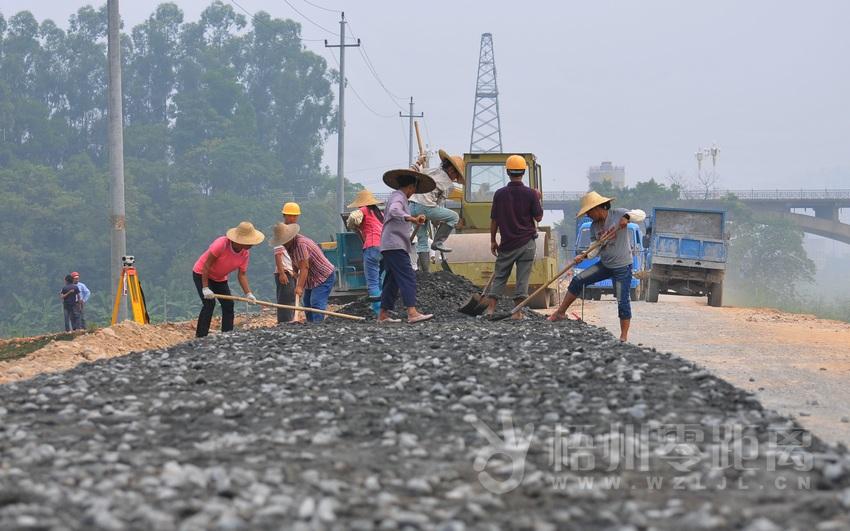 9月3日,在长洲岛防洪堤南堤上,工人们正在铺设水泥稳定碎石层.