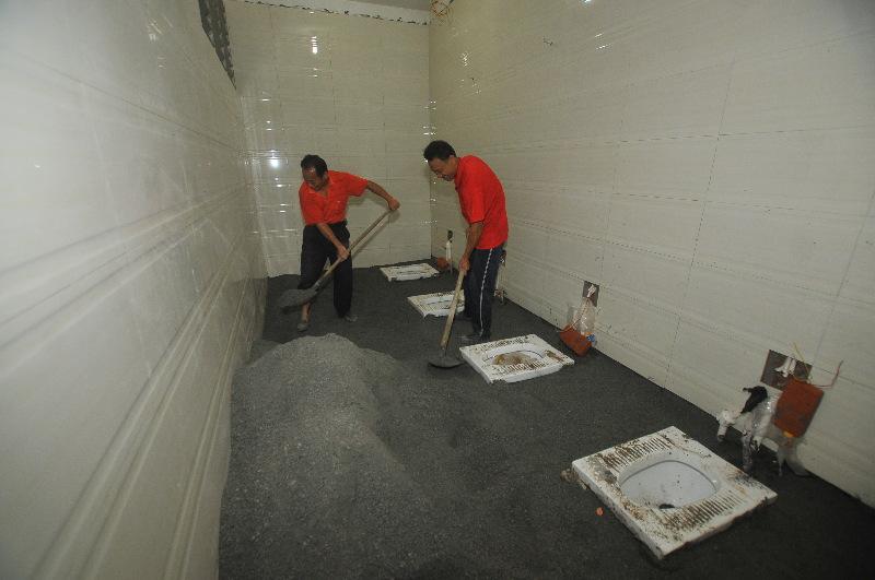 4月27日,在潘塘公园,工人在已完成节水环保改造的公厕内进行地面装修.图片