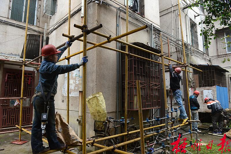 2月25日,施工人员在太和路147号住宅楼搭建脚手架。 春节假期过后,施工单位马上组织工人投入到东山冲片区的棚户区改造工作中。由于近段时间一直阴雨潮湿,外墙立面的粉刷难以开工,施工方目前正抓紧搭建楼房外围的脚手架,清理部分绿化区域,以便于下一步工作的开展。 李鸿荣 摄