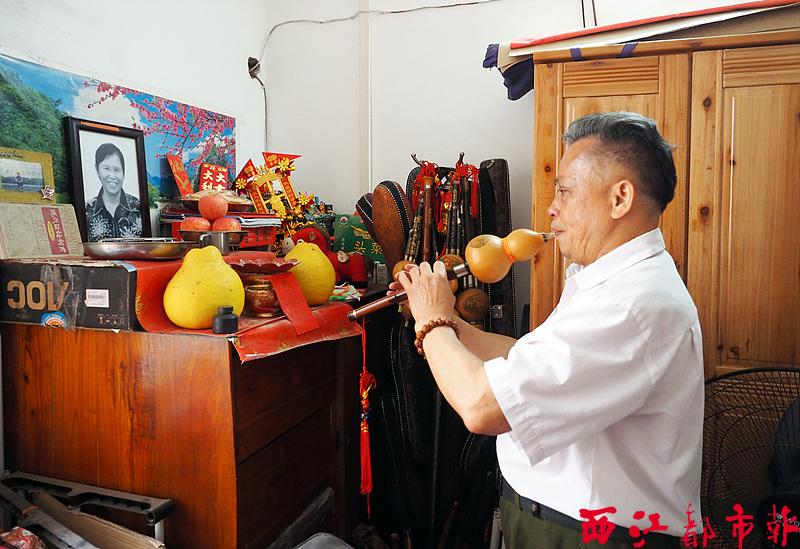 在妻子的遗像前,冼博球用葫芦丝吹奏妻子生前喜爱的歌曲,寄托自己的