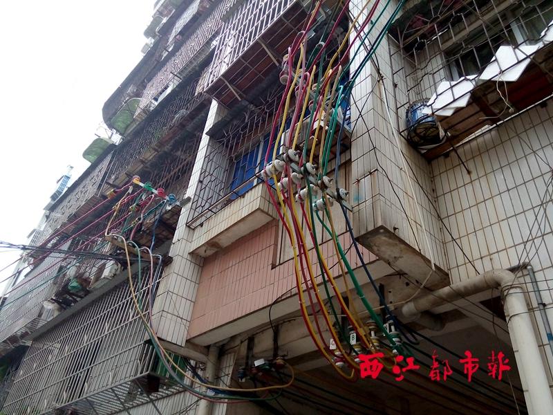 二楼窗户底下就是两排电线接驳处。朱元冬/摄  西江都市报讯(记者 朱元冬)近日,家住工厂一路43号住宅楼的居民申先生向本报反映,从住宅楼前一个变压器拉出来的电线经过他家的窗户底下,伸手即可触碰到,存在较大安全隐患,希望供电部门能解决这个问题。 7月13日,记者在43号住宅楼看到,在二楼申先生家的窗户底下,有两排五颜六色比较粗的电线在此接驳,其中一排电线就是从住宅楼前一个变压器拉出来的。变压器安装在大概三层楼高的电线杆上,旁边还竖立有另一根稍高一点的电线杆。 申先生家窗户底下的电线共有