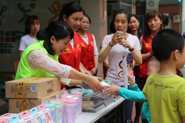 缓慢地为志愿者戴上自己参与制作的扭扭棒简易眼镜等各种造型,并与